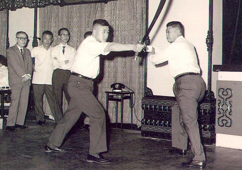 Mistr Yeung Sau-chung (1910 - 1985 / vpravo) a jeho žák Ip Tai-tak (1929 - 2004 / vlevo) demonstrují aplikaci se šavlí